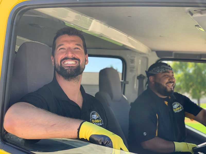 Smiling junk removal professionals in their truck