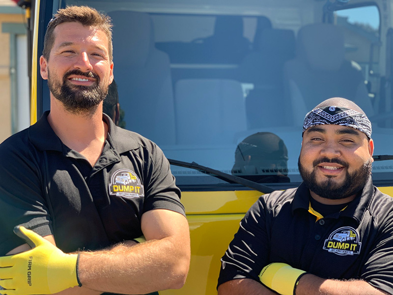 Two smiling junk removal professionals with folded arms